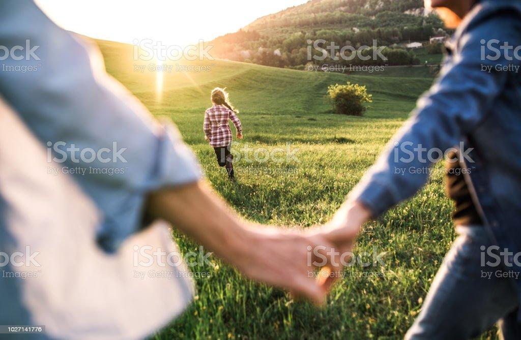 Ein kleines Mädchen mit ihren senior Großeltern Spaß draußen in der Natur bei Sonnenuntergang. - Lizenzfrei Alt Stock-Foto