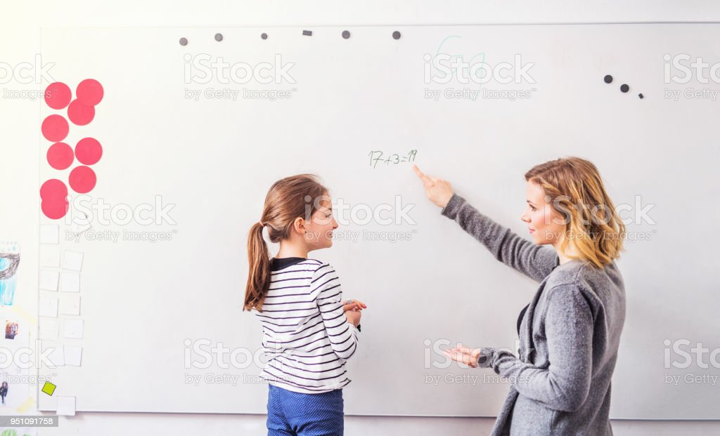 A Small Girl With Her Teacher Standing At Whiteboard At