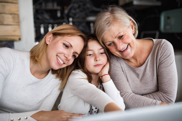 a small girl with mother and grandmother at home. - granddaughter and grandmother stock photos and pictures