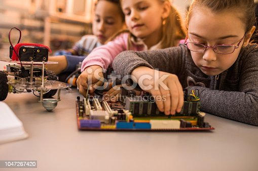 Group of kids working in laboratory. Focus is on small girl repairing computer part. Copy space.