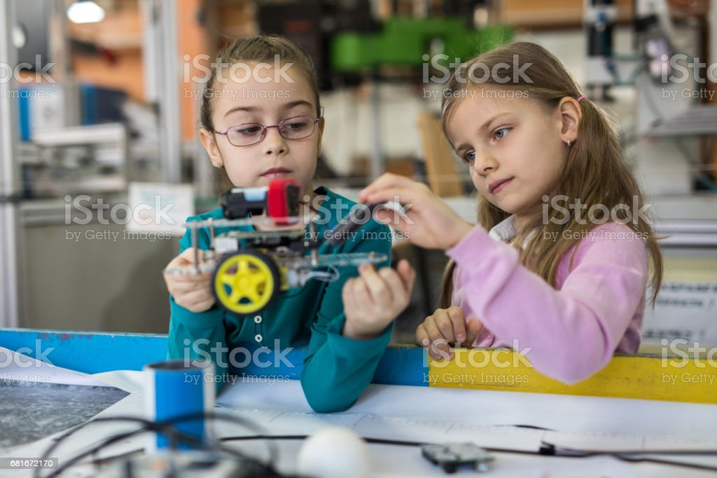Small girls cooperating while making a robot in laboratory. stock photo