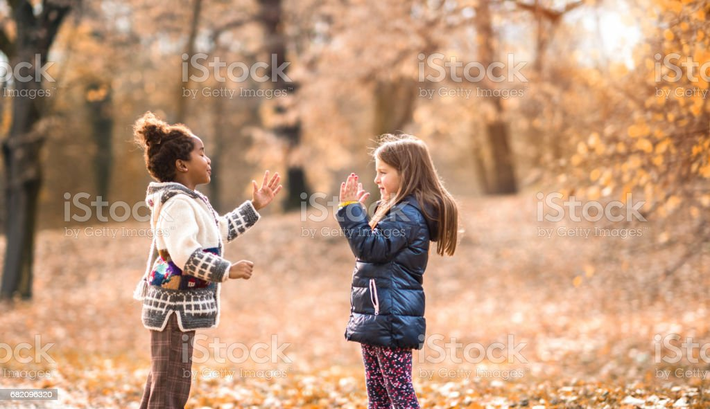 Small girls having fun while playing clapping game in nature. stock photo