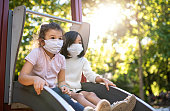 Small girls with face mask on slide on playground outdoors in town, coronavirus concept.