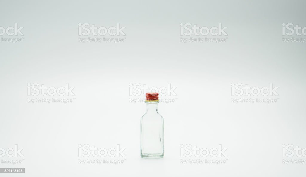 Small glass bottle with narrow neck design and red cap stock photo
