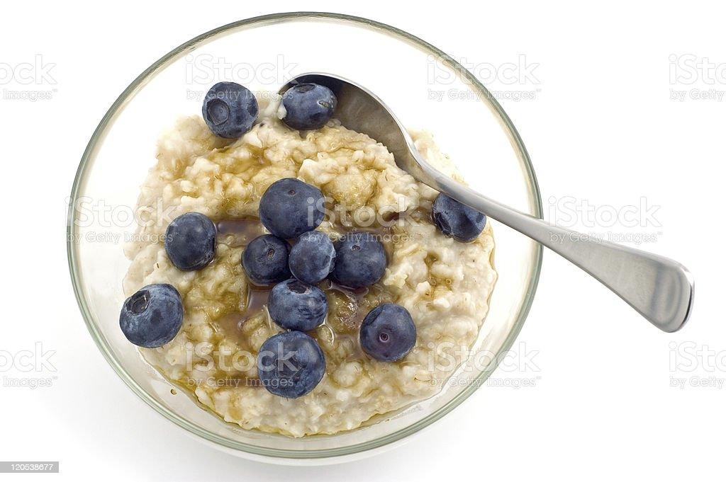 Small glass bowl of oatmeal and blueberries and silver spoon royalty-free stock photo