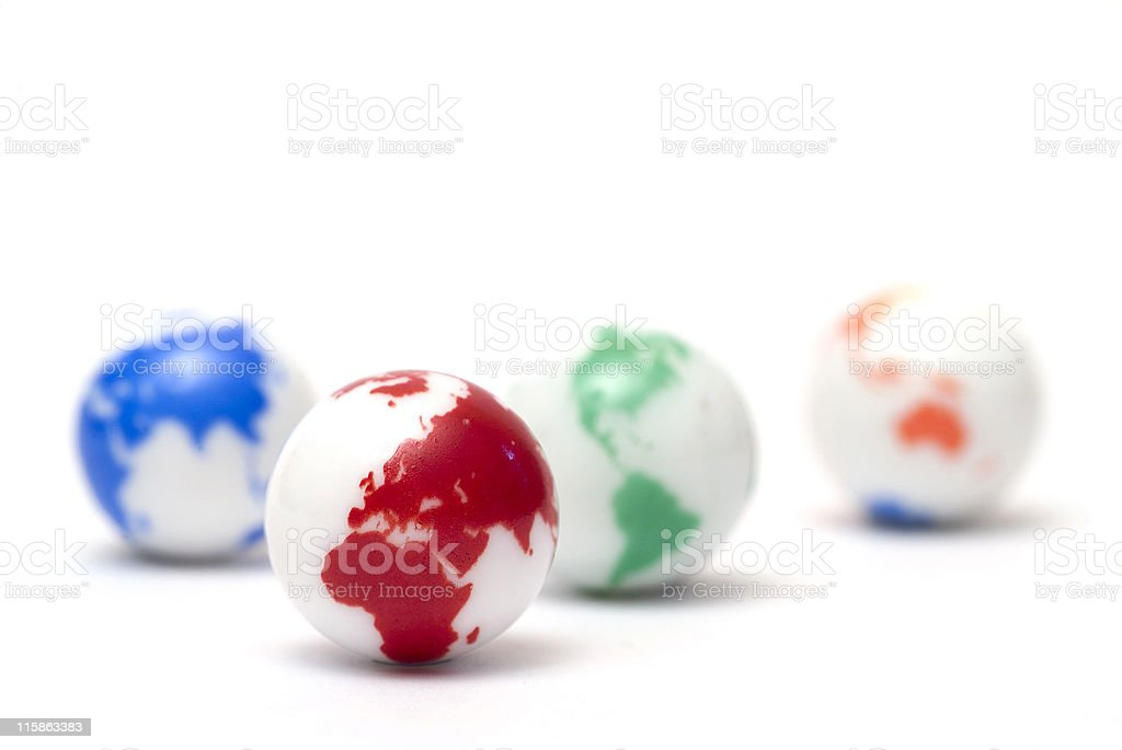 Small glass marbles with colorful globe artwork on white royalty-free stock photo