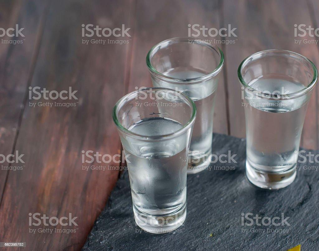 litet glas med rysk vodka och salt gurka royaltyfri bildbanksbilder