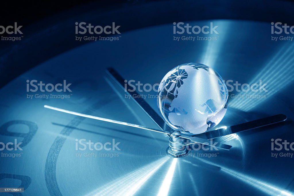 Small globe in between the hands of a clock stock photo