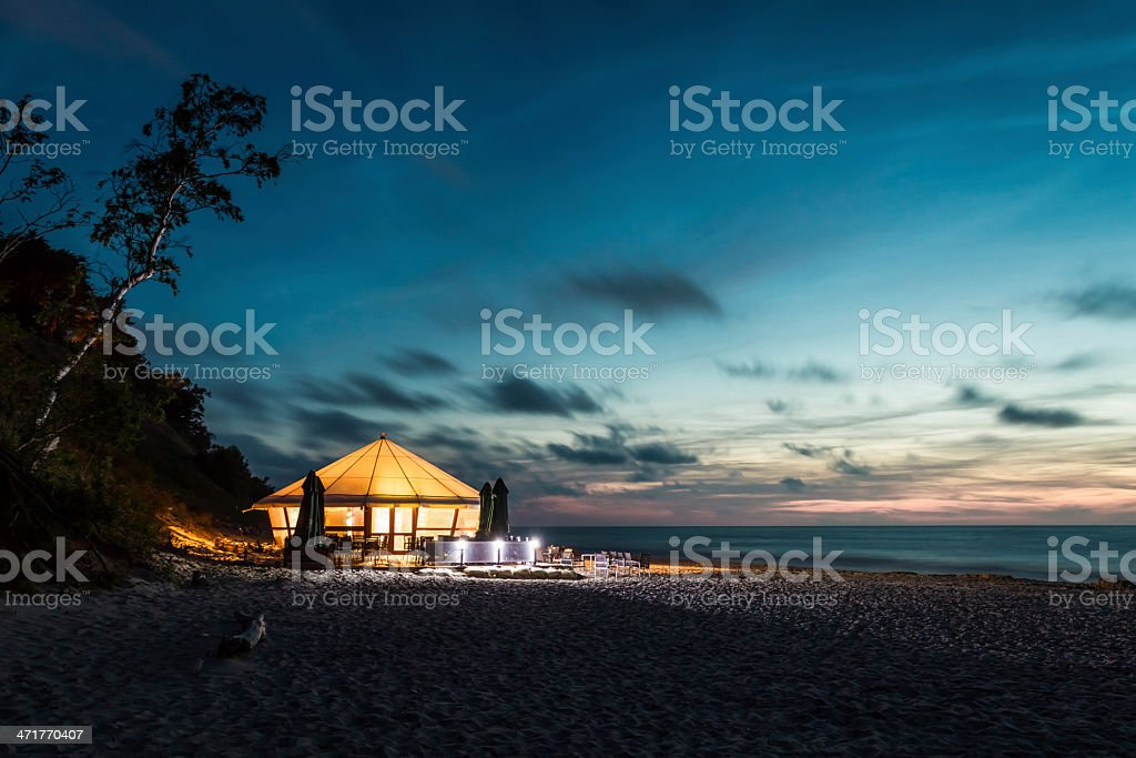 Small glowing bar by the sea at sunset stock photo