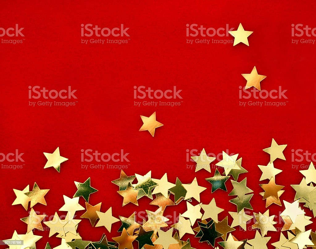 Small gold stars scattered on a red background stock photo