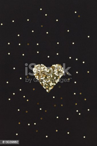 846933050istockphoto Small golden heart  made of little stars on black background. Christmas concept 815039882
