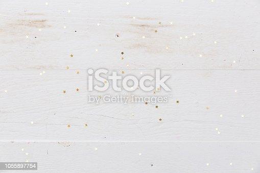 Small golden stars confetti on white wooden background.