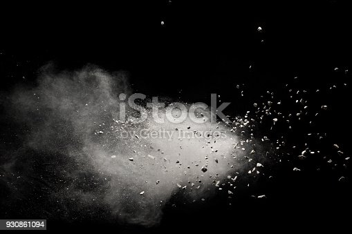 Small granite rock stone fly isolated on black background. Stone with white powder splash on dark background.