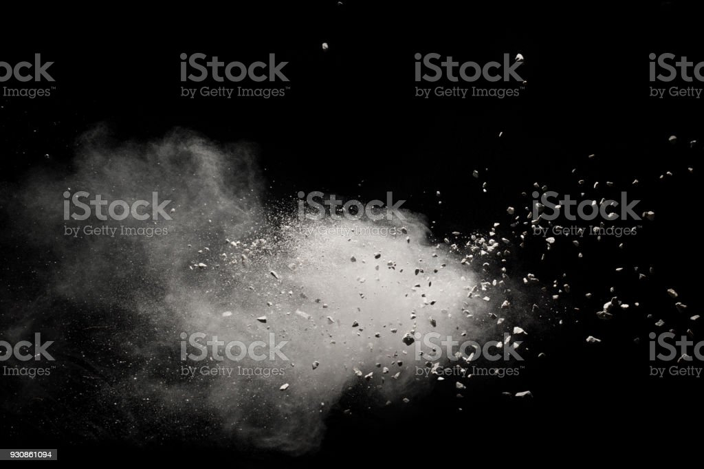 Small granite rock stone fly isolated on black background. Stone with white powder splash on dark background. stock photo