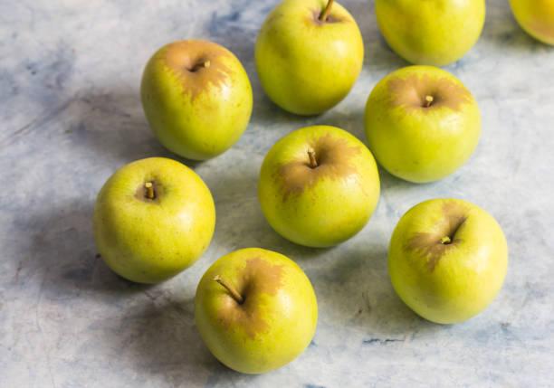 petites pommes vertes sur la surface du marbre avec mise au point sélective - golden photos et images de collection