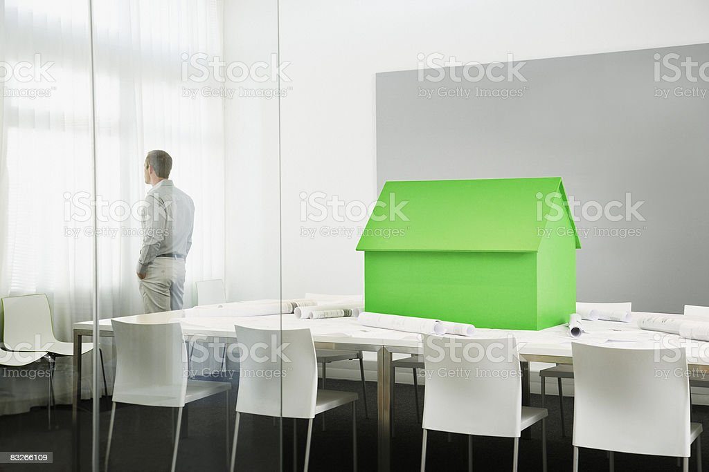 Small green model house on conference table royalty-free stock photo