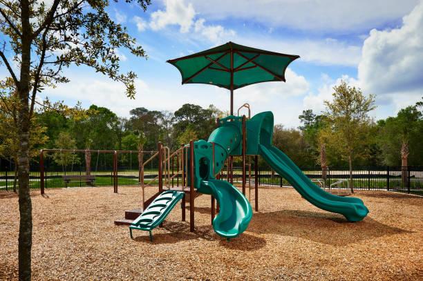 eine kleine, grüne spielplatz im freien an einem sonnigen tag - kinderspielplatz stock-fotos und bilder