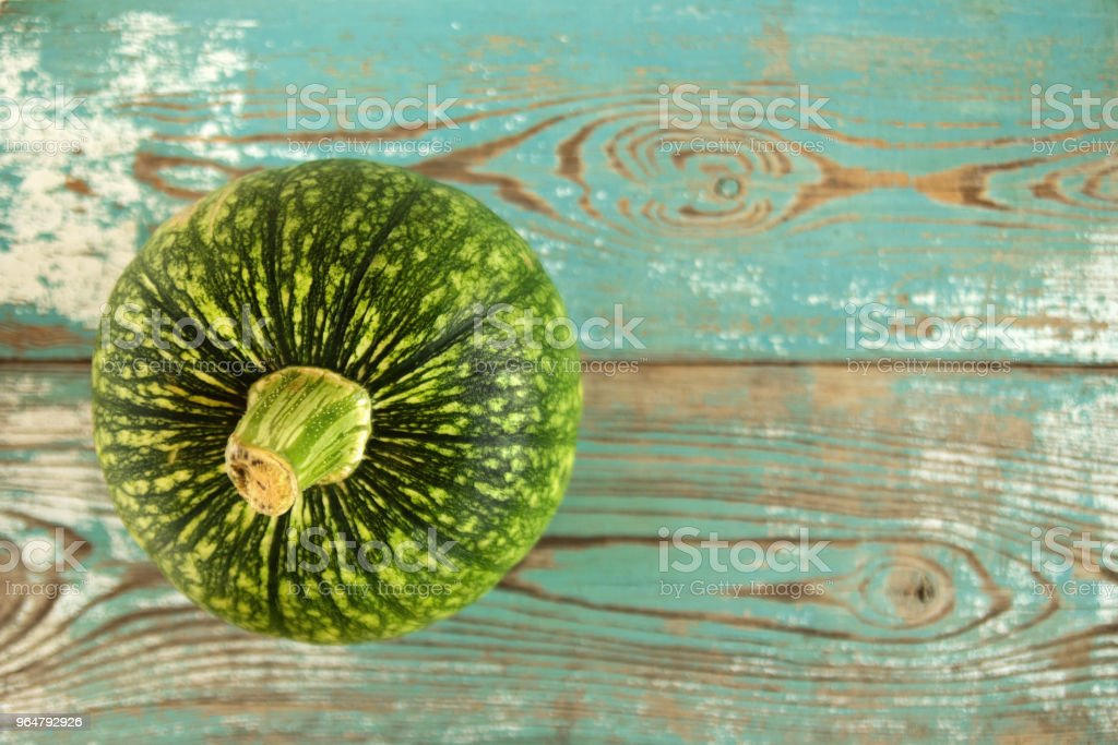 Small green pumpkin on a vintage turquoise wooden background, top view. Autumn still life. royalty-free stock photo