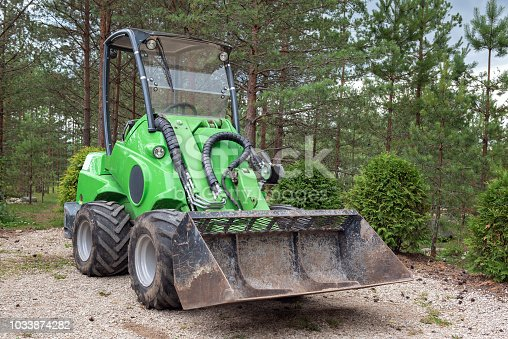 Small green tractor or skid loader parked in forest