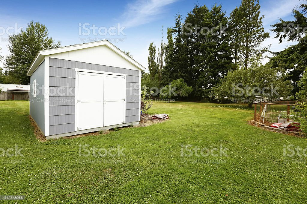 Small grey shed with white trim. Countryside real estate stock photo