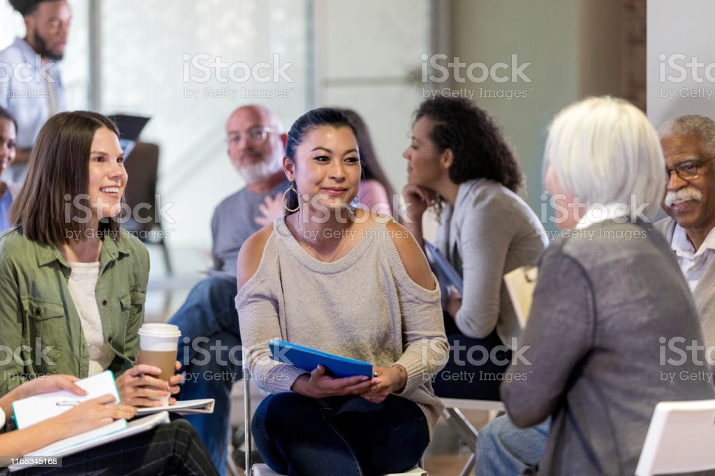The members the small group smile as the mature adult female leader...