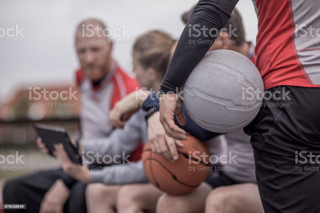 A small group of adult co-ed players of a basketball team during a street ball training session stock photo