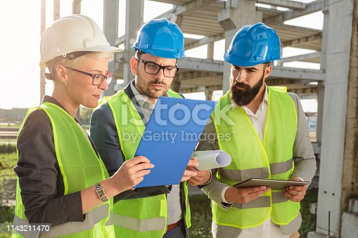 1166176793 istock photo Small group of architects and civil engineers discussing future plans and looking at project documentation 1143211470