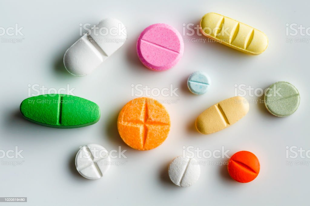 Small group of  assorted pills splitable on white background stock photo