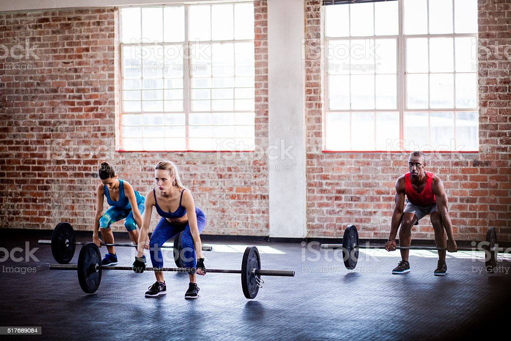 Small group of athletes on weights training class at gym stock photo