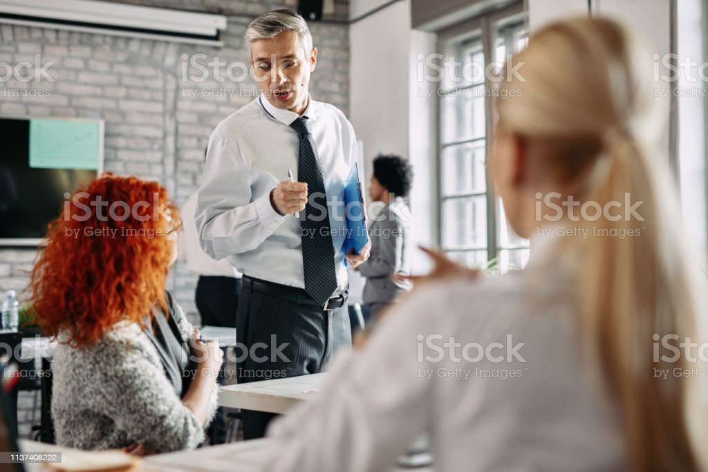 Business co-workers talking to each other while working at modern...