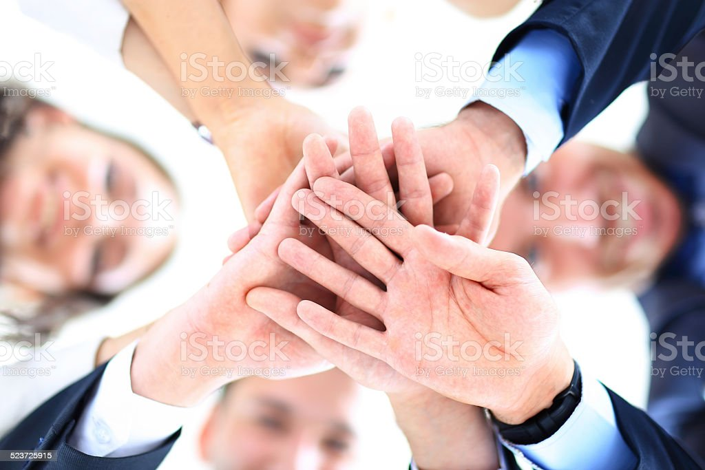 Small group of business people joining hands, stock photo