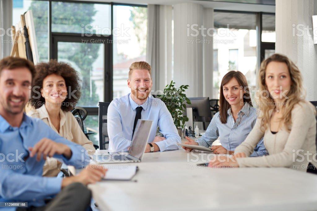 Kleine Gruppe von Geschäftsleuten posiert im Amt. – Foto