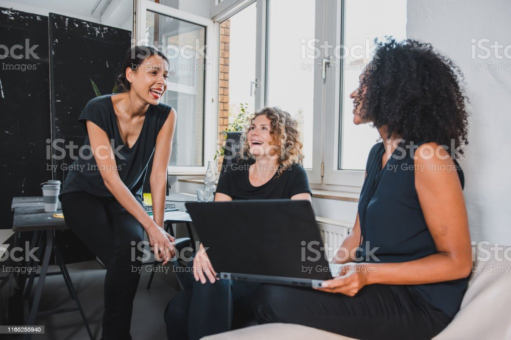 Small group of businesswomen working in the office and using a laptop
