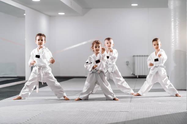kleine gruppe kaukasischer kinder in doboken, die taekwondo praktizieren und sich zum toben aufwärmen, während sie barfuß stehen. - asiatischer kampfsport stock-fotos und bilder