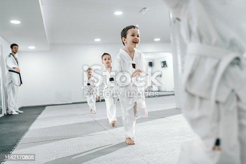 Small group of children having training at taekwondo class. All dressed in doboks. White background.