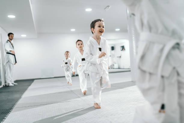 kleine gruppe von kindern, die in der taekwondo-klasse trainieren. alle in doboks gekleidet. weißer hintergrund. - asiatischer kampfsport stock-fotos und bilder