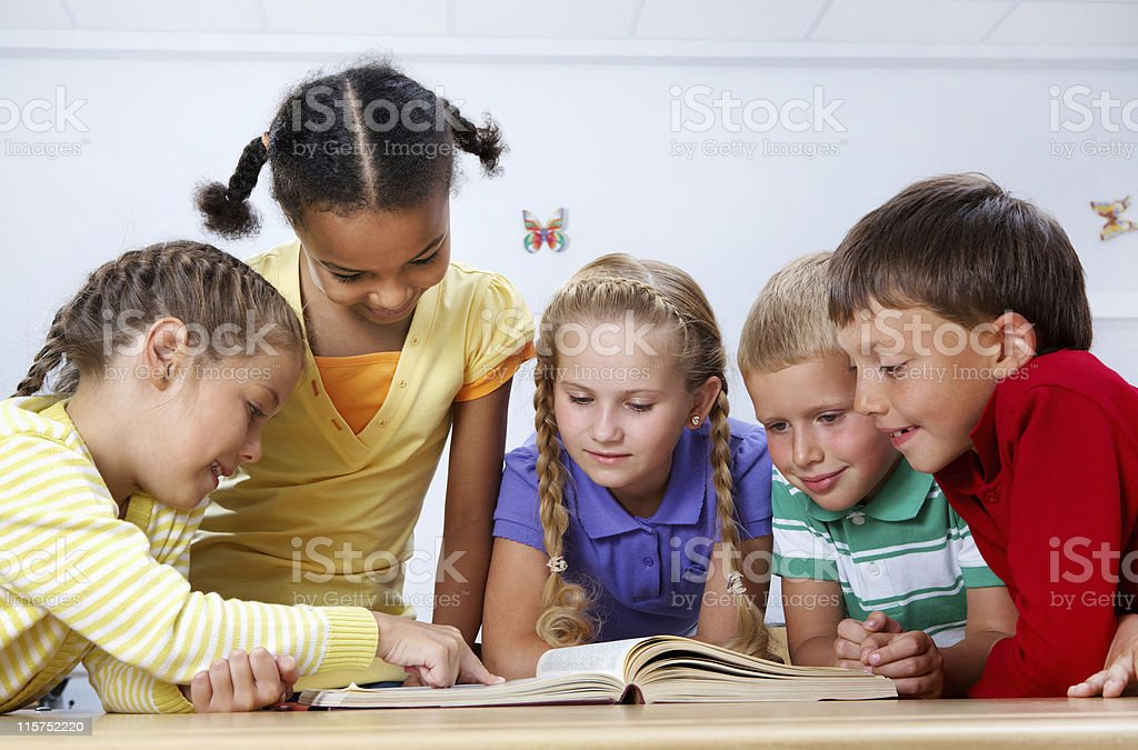 Small group of children reading a book together stock photo