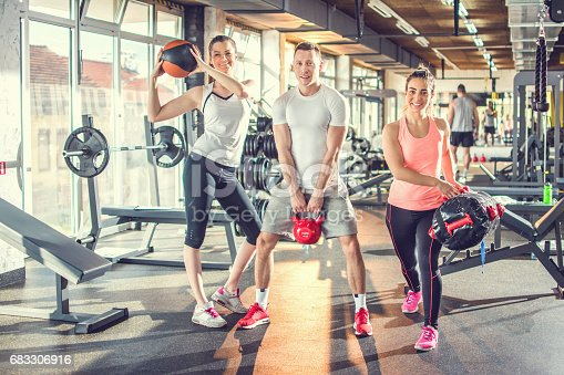 istock Small group of fit people doing exercise with kettlebell, fitness ball and exercise bag at gym. 683306916
