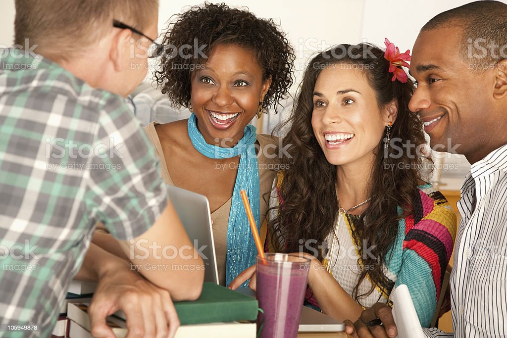 A small group of friends laughing at a table  royalty-free stock photo