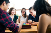A small group of friends sitting at a table, playing with a board game and enjoying time together.
