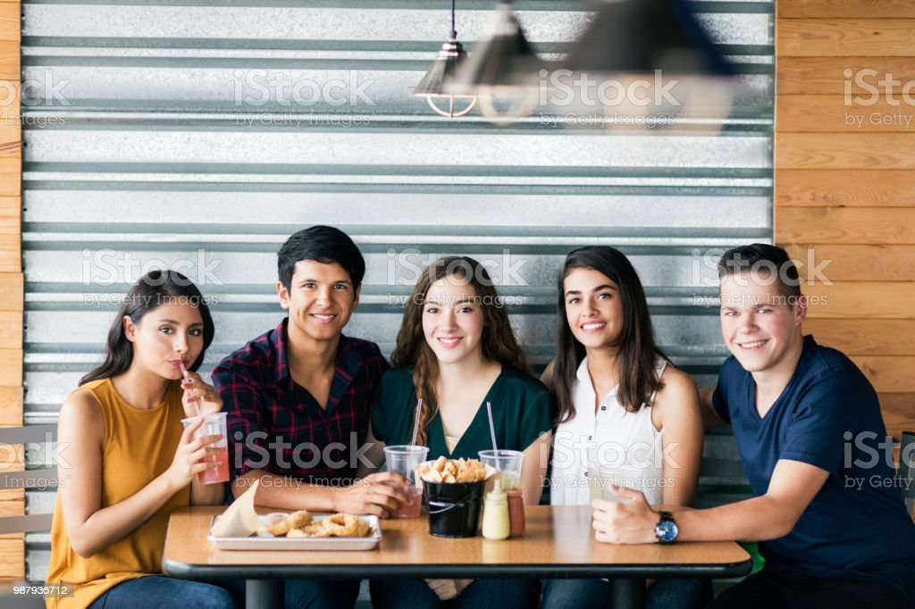 Cheerful small group of friends sitting at a table side by side,...