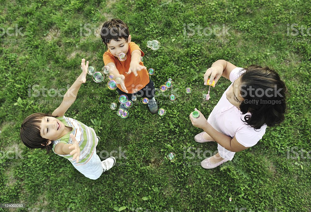 Small group of happy children making bubbles and playing together royalty-free stock photo