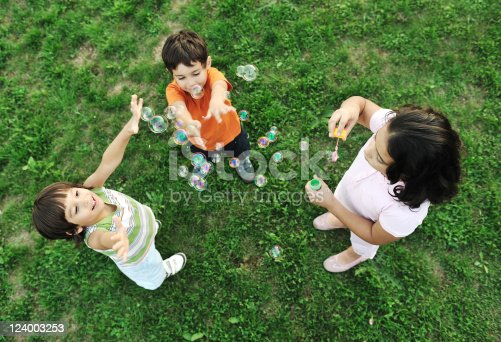618034312 istock photo Small group of happy children making bubbles and playing together 124003253