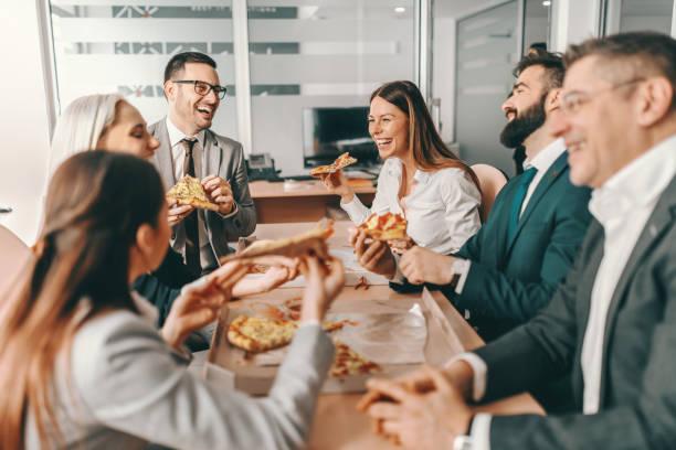 フォーマルウェアでの幸せな同僚の小さなグループは、昼食のために一緒にピザを食べるとおしゃべり。一人では、私たちはそんなに多くを行うことができ、一緒に少し行うことができます� - 昼食 ストックフォトと画像
