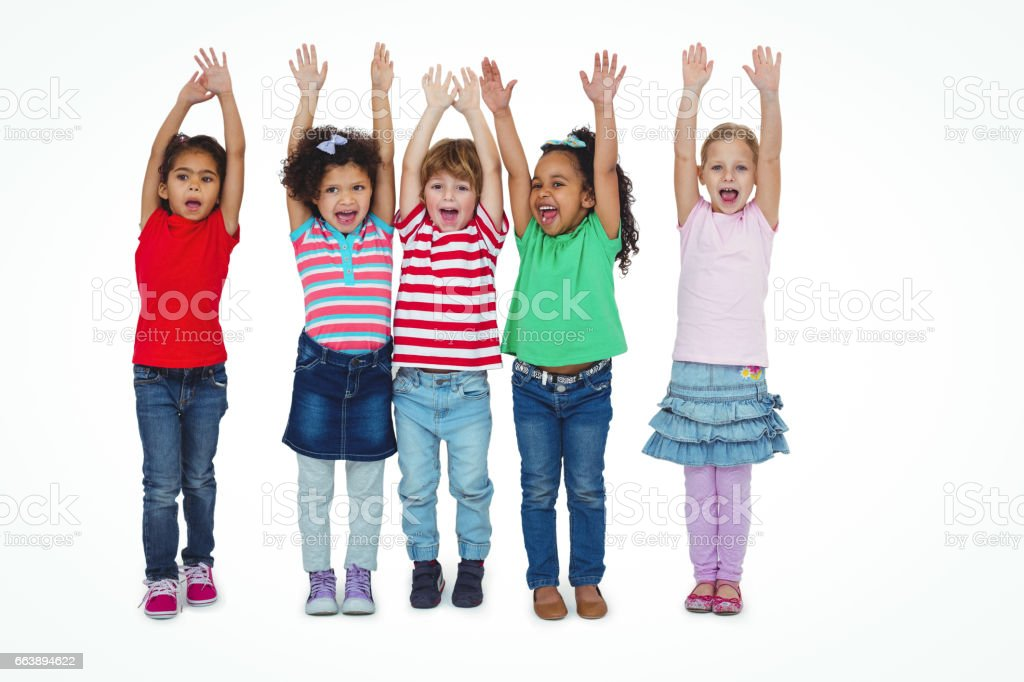 Small group of kids standing together with arms raised stock photo