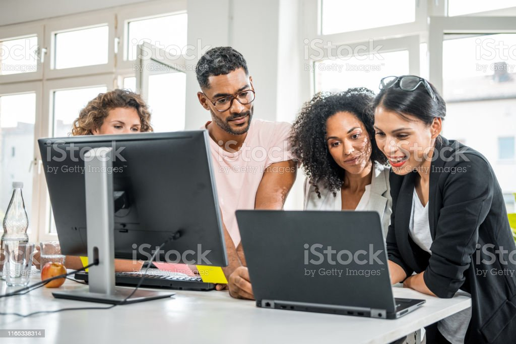 Small group of multi ethnic business people using a computer in the...