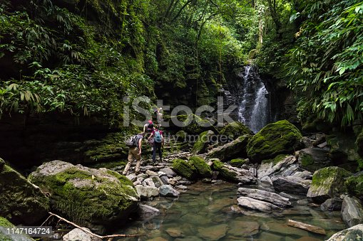 Small group of people climbing rocks at waterfall in green rainforest background.