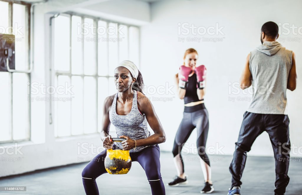 Small Group Of People Exercising in a Gym