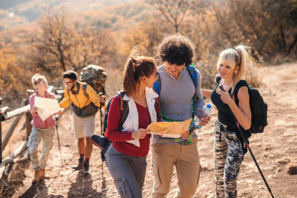 Small group of people hiking and looking at map while standing on the glade in autumn. Small group of people hiking and looking at maps while standing on the glade in autumn. field trip stock pictures, royalty-free photos & images