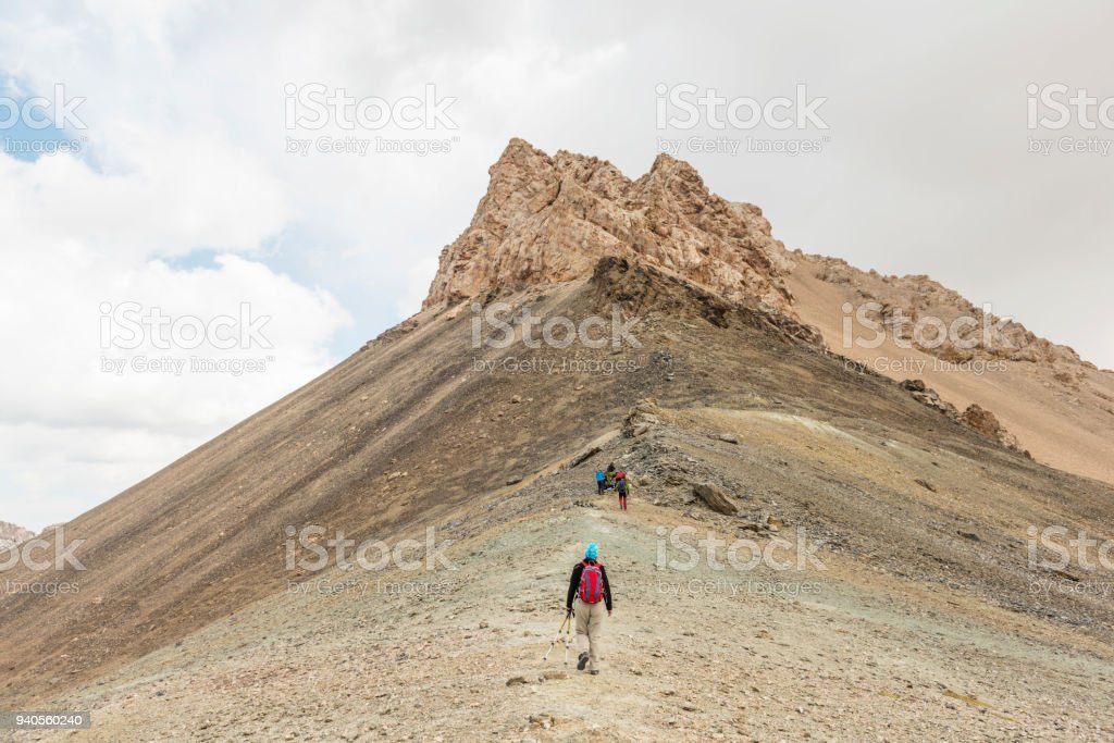 Small group of people hiking up the mountain peak stock photo